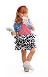 Menina feliz que está e que come doces da flor Imagem de Stock Royalty Free
