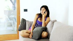 Menina feliz que fala no telefone em casa video estoque