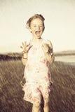 Menina feliz que funciona na chuva fotografia de stock