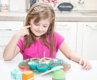 Menina feliz que funde para fora a vela do aniversário nos queques do bolo Imagens de Stock Royalty Free