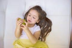 Menina feliz que guarda e que come a pera doce amarela fotos de stock