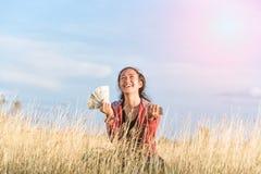 Menina feliz que guarda o dinheiro e os telefones celulares Fotografia de Stock