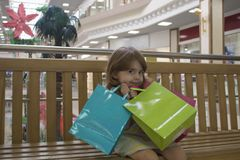 Menina feliz que guarda sacos de compras na alameda Fotos de Stock