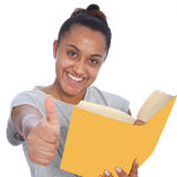Menina feliz que guarda um livro que mostra os polegares acima Fotografia de Stock