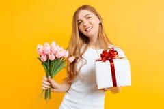 Menina feliz que guarda um ramalhete de flores bonitas e de uma caixa de presente em um fundo amarelo imagem de stock royalty free