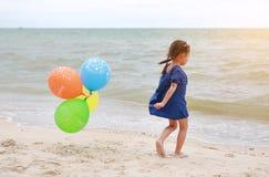 Menina feliz que joga bal?es coloridos na praia durante f?rias de ver?o imagens de stock