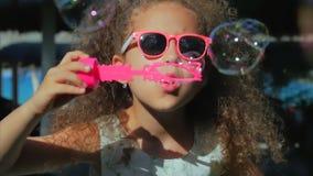 Menina feliz que joga bolhas de sabão exteriores, fundindo, tendo o divertimento no quintal nave Criança bonita no parque filme