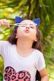 Menina feliz que joga com bolhas de sabão em uma natureza do verão, acessórios vestindo de um tigre das orelhas do azul sobre sua Imagem de Stock