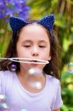 Menina feliz que joga com bolhas de sabão em uma natureza do verão, acessórios vestindo de um tigre das orelhas do azul sobre sua Fotografia de Stock