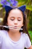 Menina feliz que joga com bolhas de sabão em uma natureza do verão, acessórios vestindo de um tigre das orelhas do azul sobre sua Imagem de Stock Royalty Free