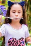 Menina feliz que joga com bolhas de sabão em uma natureza do verão, acessórios vestindo de um tigre das orelhas do azul sobre sua Fotos de Stock