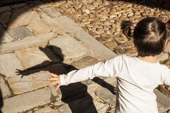 Menina feliz que joga com sua sombra Imagens de Stock
