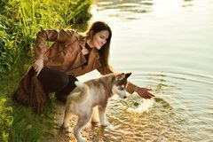 Menina feliz que joga com um cão de cachorrinho ronco no riverbank no outono fotos de stock
