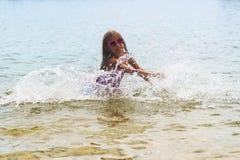 Menina feliz que joga em ondas de água pouco profunda menina que joga nas ondas do mar, menina que tem o divertimento em ondas do fotos de stock