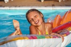 Menina feliz que joga na água azul da piscina Imagem de Stock Royalty Free