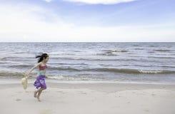 Menina feliz que joga na praia fotos de stock royalty free