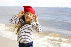 Menina feliz que joga na praia Imagens de Stock