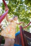 Menina feliz que joga no campo de jogos do baixo ângulo Fotografia de Stock Royalty Free