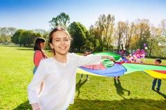 Menina feliz que joga o jogo engraçado exterior com amigos Fotografia de Stock Royalty Free