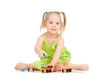 Menina feliz que joga o trem do brinquedo no assoalho imagem de stock