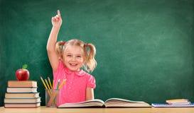 Menina feliz que levanta a mão na sala de aula imagem de stock