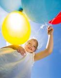 Menina feliz que mantém balões contra o céu Imagem de Stock Royalty Free