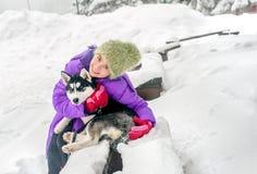 Menina feliz que mantém seu cão de cachorrinho ronco na neve Fotografia de Stock