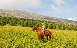 Menina feliz que monta um cavalo fotografia de stock