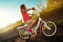 Menina feliz que monta uma bicicleta foto de stock royalty free
