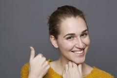 Menina feliz que mostra um produto acima com gesto de mão discreto Imagem de Stock