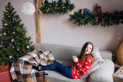 Menina feliz que olha fluindo o índice na linha em um telefone esperto que senta-se em um sofá no inverno em casa fotos de stock royalty free