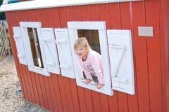 Menina feliz que olha fora de um indicador do celeiro. Foto de Stock