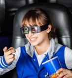 Menina feliz que olha o filme 3D no teatro Imagens de Stock