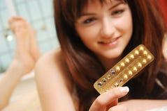 Menina feliz que olha seus comprimidos contraceptivos fotos de stock royalty free