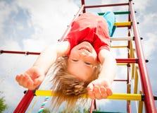 Menina feliz que pendura de um gym de selva em um jardim do verão Imagens de Stock