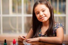 Menina feliz que pinta seus pregos Foto de Stock