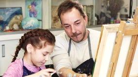 Menina feliz que pinta uma imagem com seu pai