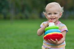Menina feliz que prende uma pirâmide do brinquedo Imagem de Stock