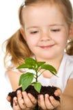 Menina feliz que prende uma planta nova com solo foto de stock royalty free
