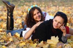 Menina feliz que relaxa nas folhas de outono amarelas Fotografia de Stock Royalty Free