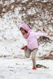 Menina feliz que salta na neve Fotografia de Stock Royalty Free