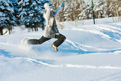Menina feliz que salta na neve no inverno Imagens de Stock Royalty Free
