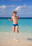 Menina feliz que salta na praia Fotografia de Stock