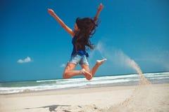 Menina feliz que salta na praia Fotografia de Stock Royalty Free