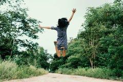 Menina feliz que salta no trajeto nas madeiras Imagem de Stock