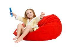 Menina feliz que senta-se em uma cadeira, penteando o cabelo Fotografia de Stock