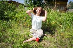 Menina feliz que senta-se na grama com uma xícara de café vermelha no fundo do acampamento, manhã do verão fotografia de stock royalty free