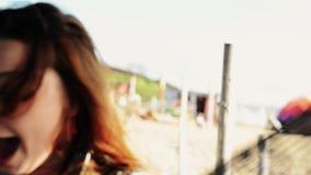 Menina feliz que senta-se na rede no sorriso da praia in camera Dia ensolarado carefree filme
