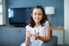 Menina feliz que senta-se no sofá e que usa o telefone celular na sala de visitas Imagens de Stock Royalty Free