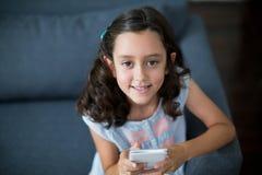 Menina feliz que senta-se no sofá e que usa o telefone celular na sala de visitas Imagem de Stock